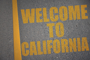 asphalt road with text welcome to california near yellow line