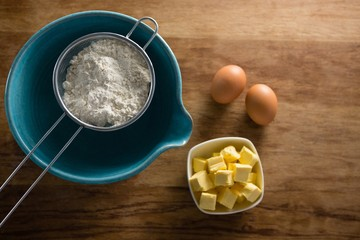 Flour in stainer with eggs and cheese