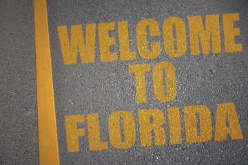 asphalt road with text welcome to florida near yellow line