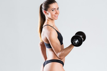 Beautiful fitness woman with dumbbells isolated.