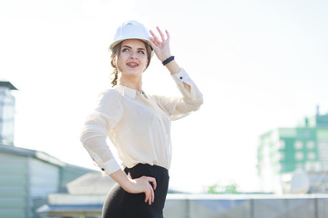 Beautiful businesslady in white blouse, watch, helmet and black skirt stand on the roof