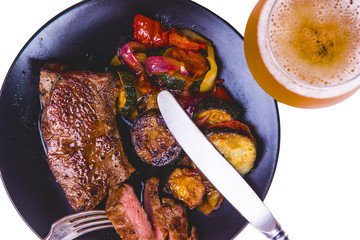 Classic New York steak with fried vegetables on a black plate and a glass of light beer - isolated