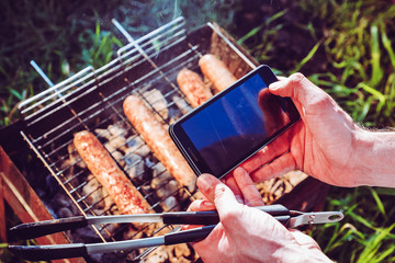 makes a photo on a smartphone Grilling sausages on BBQ.