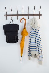Hoodie, umbrella and bag hanging on hook
