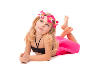 Cute pretty little girl in black bikini, pink skirt and pink wreath, lies