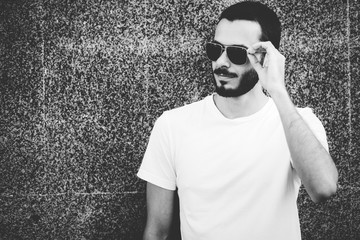 Young man wearing white blank t-shirt with beard in glasses, standing on the street on city background. Street photo