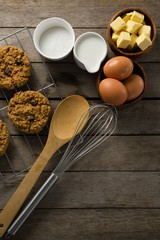 Fresh baked cookies, whisk, eggs, flour on wooden table