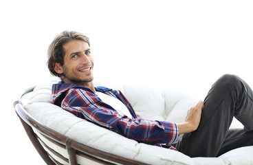 successful guy sitting in a large round comfortable chair.