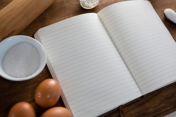 Book, eggs, flour and rolling pin kept on a table