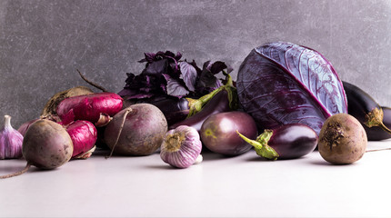 Assortment of Purple and Red vegetables on a stone background.