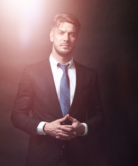 Handsome business man isolated on black with arms crossed