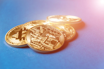 Several coins of bitcoins lie on a blue background with bright glow, toning and blurring. Crypto currency concept