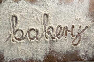 The word bakery written on sprinkled flour