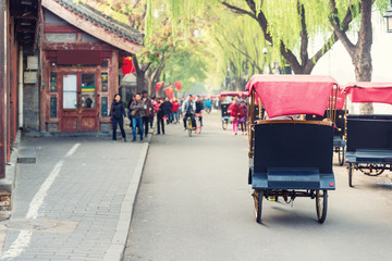 Photo sur Toile Pékin Tourists riding Beijing traditional rickshaw in old China Hutongs in Beijing, China.
