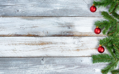 Christmas evergreen branches and red ornaments on rustic knotty white wooden background