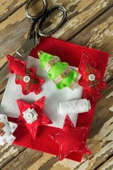 Handmade christmas trees and craft material on wooden plank