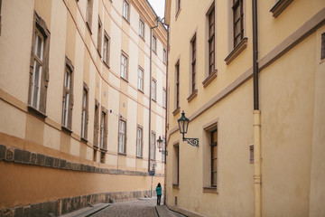 Tourist girl in green jacket walks along beautiful deserted narrow street in Prague between two historic buildings