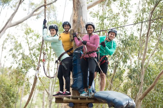 Friends ready to zip line in park on a sunny day