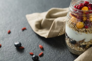 Yogurt with pomegranates and golden berries in glass jar