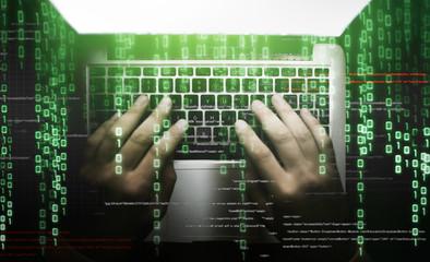 Hacker at work on laptop keyboard