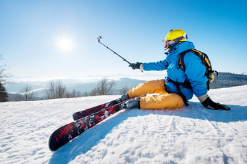 Shot of a skier sitting on the ski slope taking a selfie using selfie stick resting relaxing extreme recreation active lifestyle activity technology smart phone mobility internet online concept
