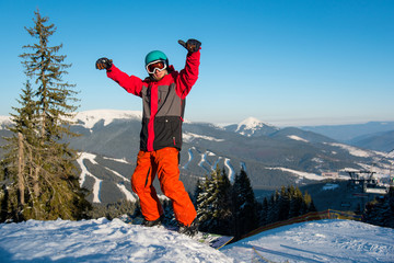 Excited snowboarder standing on the slope with his arms in the air in victorious gesture copyspace emotions recreation happiness positivity people recreational resort Bukovel
