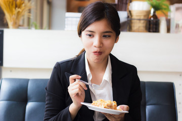 Asian business woman in relax time and eating apple pie in coffee shop. Hand holding  spoon used to eat pie. Apple pie, regional variation apple tart, which the principal filling ingredient is apple.