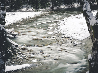 Flowing River in Winter Season Framed by Forest Trees