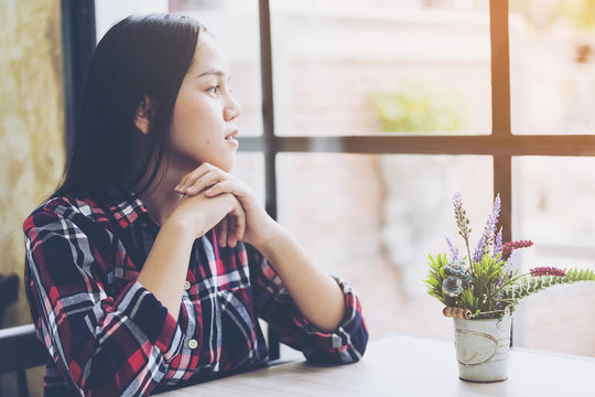 Beautiful asian woman gestures thinking and looking through cafe window with copy space,Courageous female student looking at the window. Sad and depressed Hipster girls or business woman sitting alone