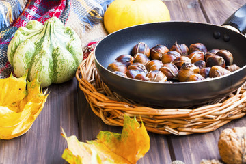 Roasted chestnuts in a pan with autumn pumpkins and dried maple leaves on wooden tray and board, fall background concept