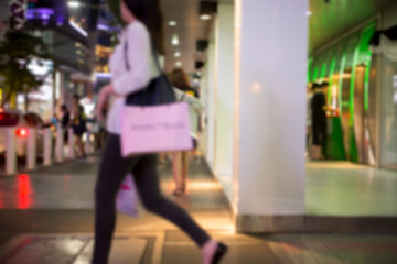 Blurred concept woman walking with shopping bag in city in motion blur