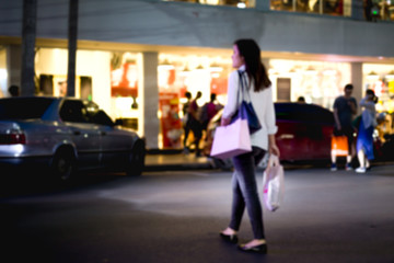 Unidentified woman crossing the road with shopping bag l