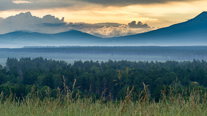 Poster Turquoise Dramatic sunrise in the mountains with thick evergreen forest in foreground covered with fog, Altai Mountains, Kazakhstan