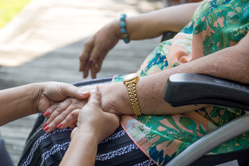 Elderly woman in wheelchair holding hands with caregiver