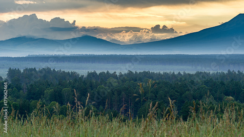 dramatic sunrise in the mountains with thick evergreen forest in