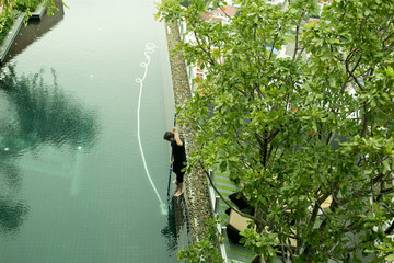 Man cleaning tropical resort swimming pool with vacuum tube cleaner
