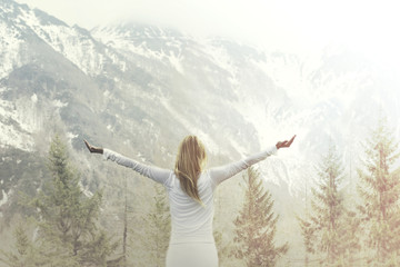 woman taking a breath in front of a majestic mountain