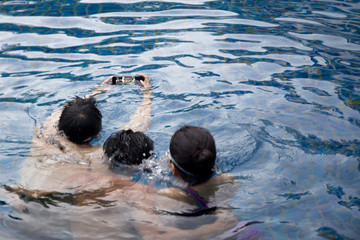 Selected focus on waterproof cell phone group of friends taking picture in swimming pool