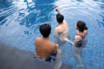 Group of friends taking selfie in swimming pool resort with waterproof cell phone