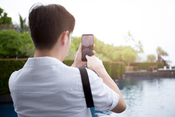 Young man tourist taking photos of landscape with cell phon