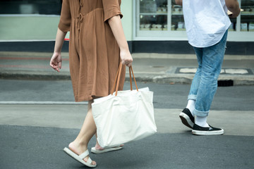 Street fashion woman with brown dress with white cotton blank canvas cotton tote bag walking on the street