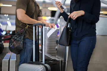 Selected focus on ticket couple standing at airport Check-in desk