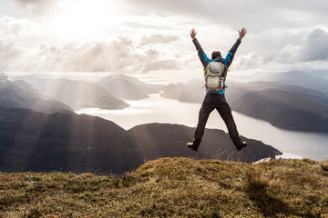 Man reaching summit and leaping for joy. Stunning view to coastal mountains and fjords. Hellandsnuten, Sandsfjord, Norway.
