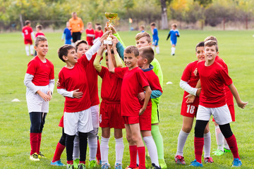 Kids soccer football -  children players celebrating with a trophy after match on soccer field
