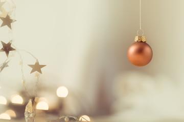 Eine hängende Kupfer Weihnachtskugel mit weichem Lichter Bokeh und Sterne