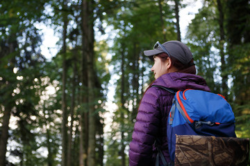 Photo of tourist woman with backpack on blurred background of trees