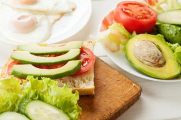 Sliced avocado, tomatoes, cucumber on a fresh ciabatta bread