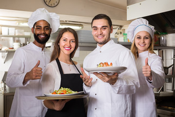 Waitress and crew of professional cooks posing at restaurant