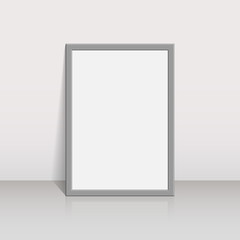 Picture frame on a white wall 3d background design for your content. Blank white paper poster in grey frame standing on a floor. Mock-up template for your design.