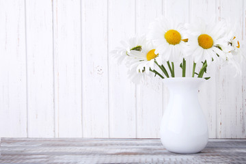 Bouquet of chamomile flowers in vase on wooden table